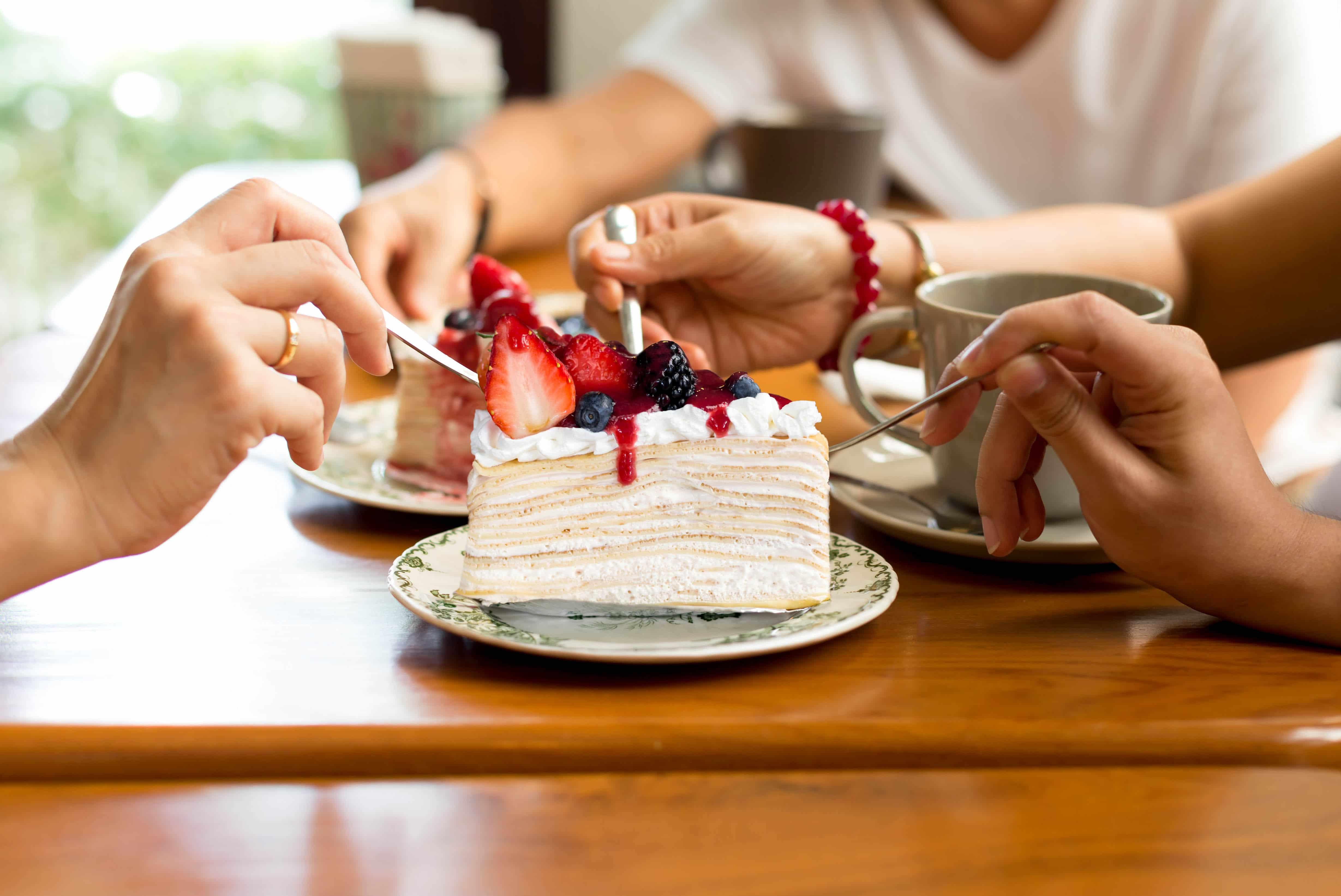 Grupa znajomych ma ochotę na słodycze i je ciasto.