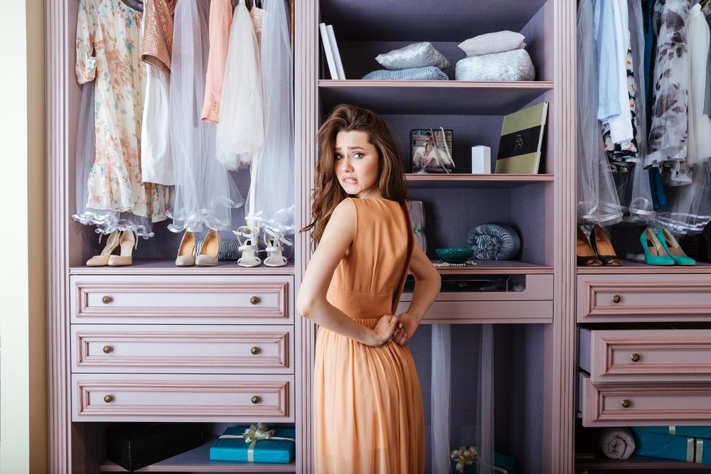 Dziewczyna stoi przed szafą i nie może dopiąć sukienki.