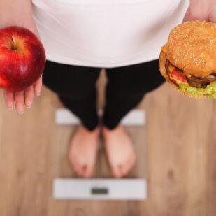 Jak się odchudzać – dziewczyna z jabłkiem i hamburgerem w dłoniach