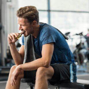 Mężczyzna je przed treningiem na siłowni