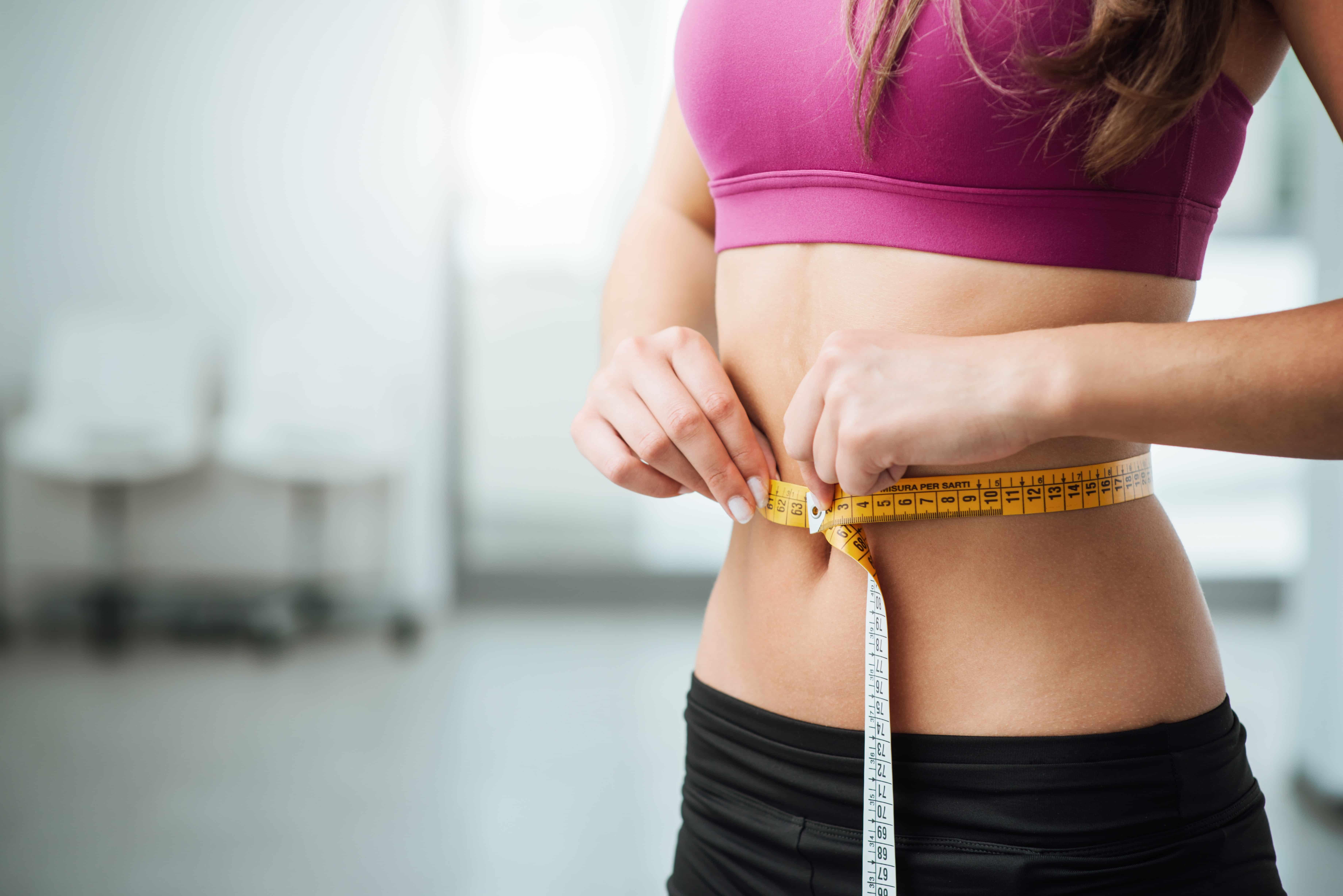 Kobieta z płaskim brzuchem mierząca obwód talii.