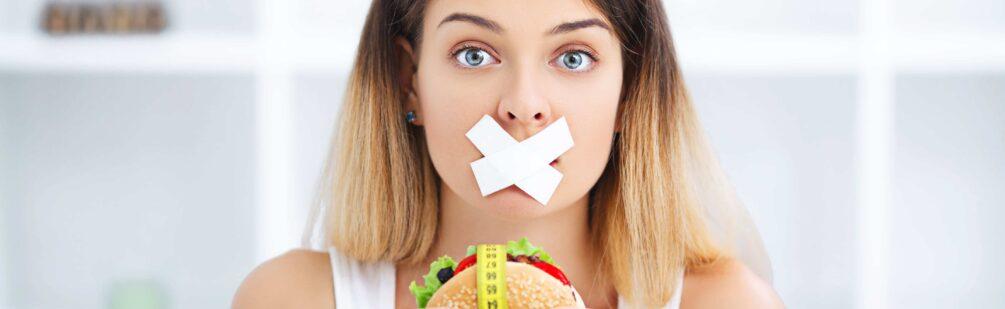 Dziewczyna odmawia sobie burgera, bo chce, żeby jej dieta była skuteczna.
